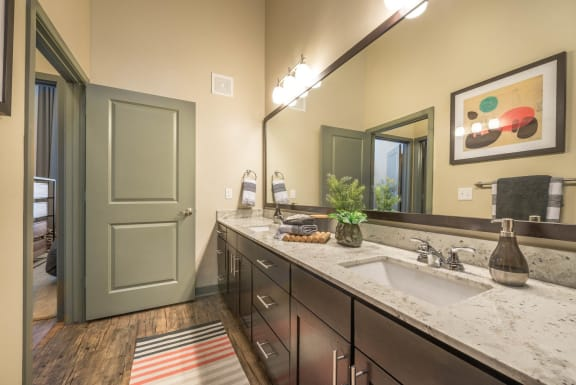 View of bathroom with double sinks and granite countertops, framed mirrors, and wood flooring