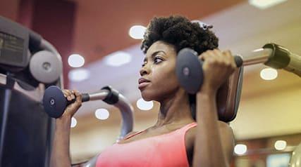 African American woman using exercise machine_Cedars at Carver Park Galveston, TX