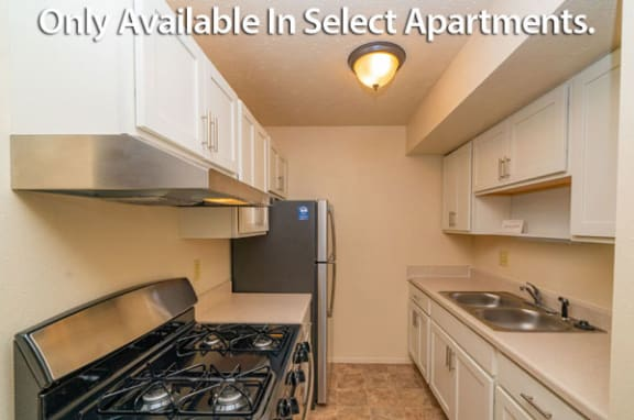 Kitchen with Stainless Steel Appliances and Shaker-style Cabinets at Old Farm Apartments in Elkhart, IN