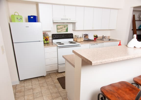 Kitchen photo with light wood cabinetry, white appliances and tan counter tops