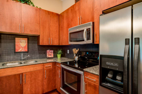 Stainless steel appliances including built-in microwave, refrigerator, and dishwasher at Eon at Lindbergh, Atlanta, GA