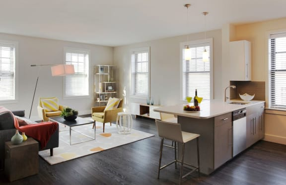 Open Concept Living, Dining and Kitchen with hard surface flooring, large windows and prep island at Gatehouse 75, Charlestown, MA, 02129