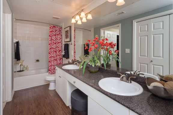 Master bathroom with floating vanities, quartz countertops, backlit vanity mirror, walk-in shower with Euro shower door and quartz-topped bench seat at The Plaza Museum District, Houston, TX, 77004