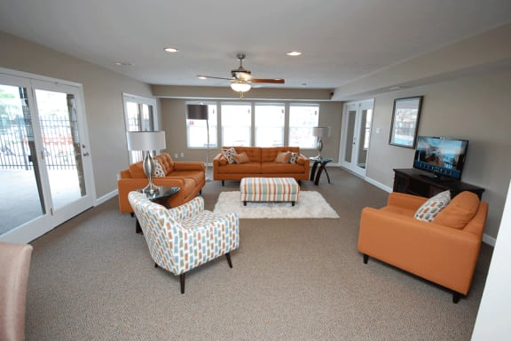 Clubhouse room with orange chairs, brown carpet and beige walls.  TV to the right of photo on wall.