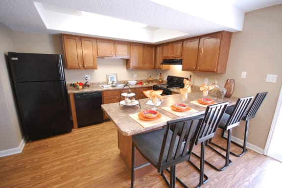 Kitchen with medium wood cabinetry, beige countertops, black appliances with a breakfast bar.  Breakfast bar is set with place settings and 4 chairs.