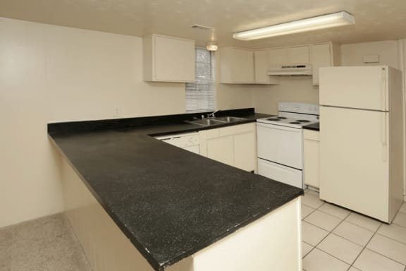 Fully equipped white kitchen wiht black countertops and white tile floor.