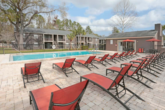 Expansive sundeck and pool. Red lounge chairs are lined up on the sundeck.