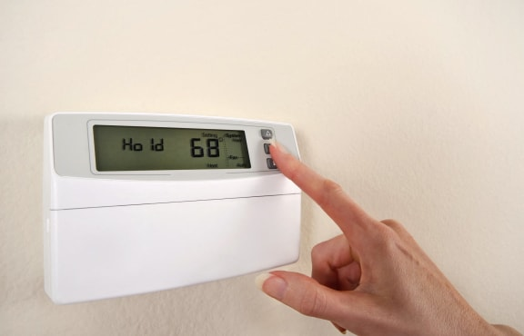 Person using electric thermostat-Oakland Heights Apartments Exterior, Kansas City, MO