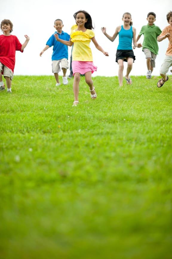 Children running in a field-Longfellow Heights Apartments, Kansas City, MO