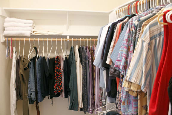 Walk in closet filled with clothes on hangers-Longfellow Heights Apartments, Kansas City, MO