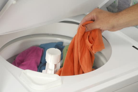 Person putting clothes in washer machine-Tremont Pointe Apartments, Cleveland, OH 44113