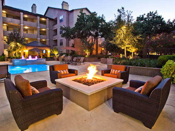 Cozy outdoor fire pit by the pool at apartments on Preston Road