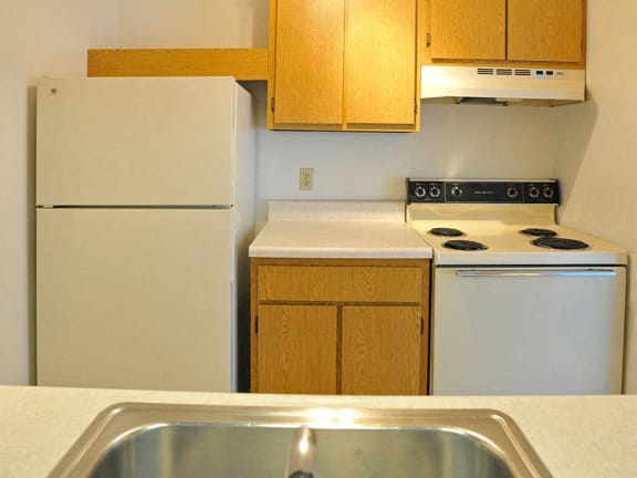 White kitchen appliances at Charter Oaks Apartments in Davison, MI