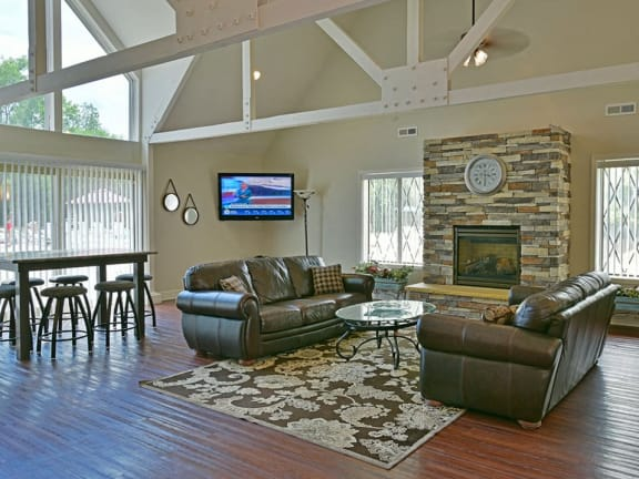 Large clubhouse with fireplace and TV at Charter Oaks Apartments in Davison, MI