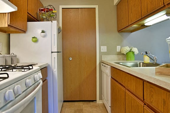 Galley Style Kitchen with White Appliances at Stone Ridge Apartments, Wixom