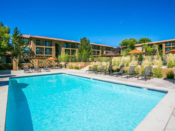 Outdoor Swimming Pool with Sundeck and Lounge Area at Paseo Del Rio Apartments For Rent in Albuquerque, NM