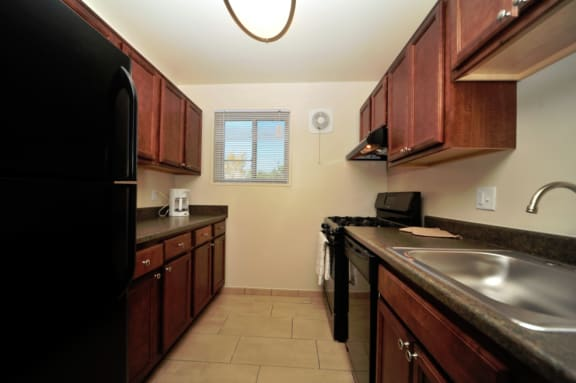 kitchen at Overlook apartments in Hyattsville MD with black appliances and dark wood cabinets