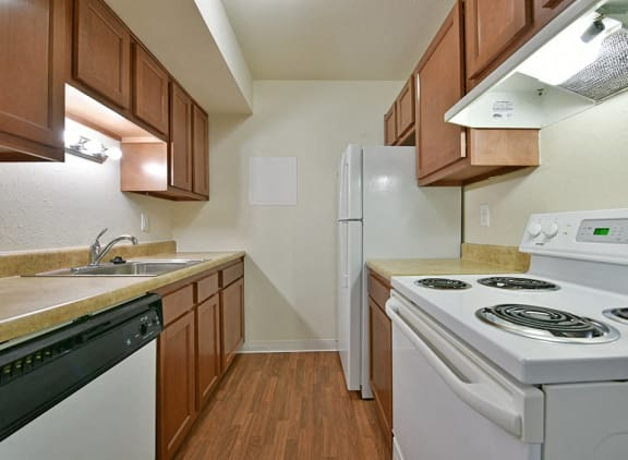 White kitchen appliances at Perry Place Apartments in Grand Blanc, MI