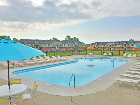Outdoor swimming pool with sundeck at Grand Bend Club apartments in Grand Blanc, MI