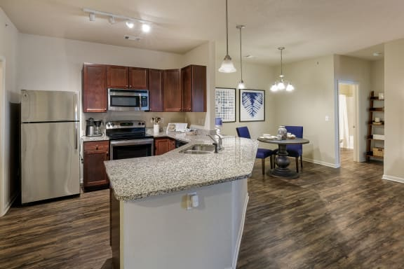 Glenbrook Apartments energy efficient stainless steel appliances including a glass-topped stove and a refrigerator with ice maker