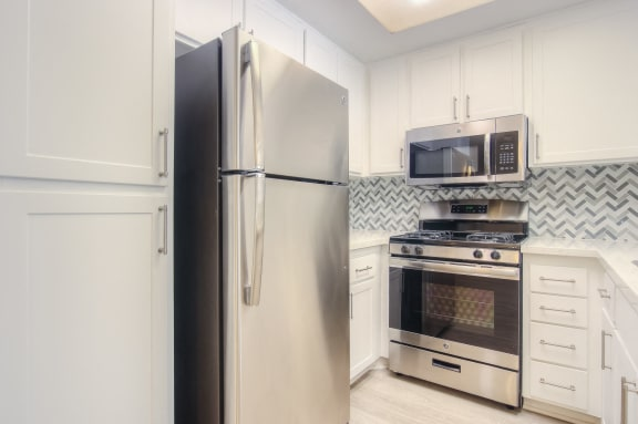 Renovated kitchen featuring white cabinet, countertops and stainless steel appliances.