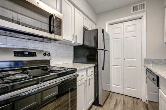 Upgraded Units Available with Sleek Black Appliances, Vinyl Plank Wood Flooring, Ceramic Tile Backsplash and Granite Like Countertops at The Edge of Germantown Apartments Home, Memphis, TN 38120