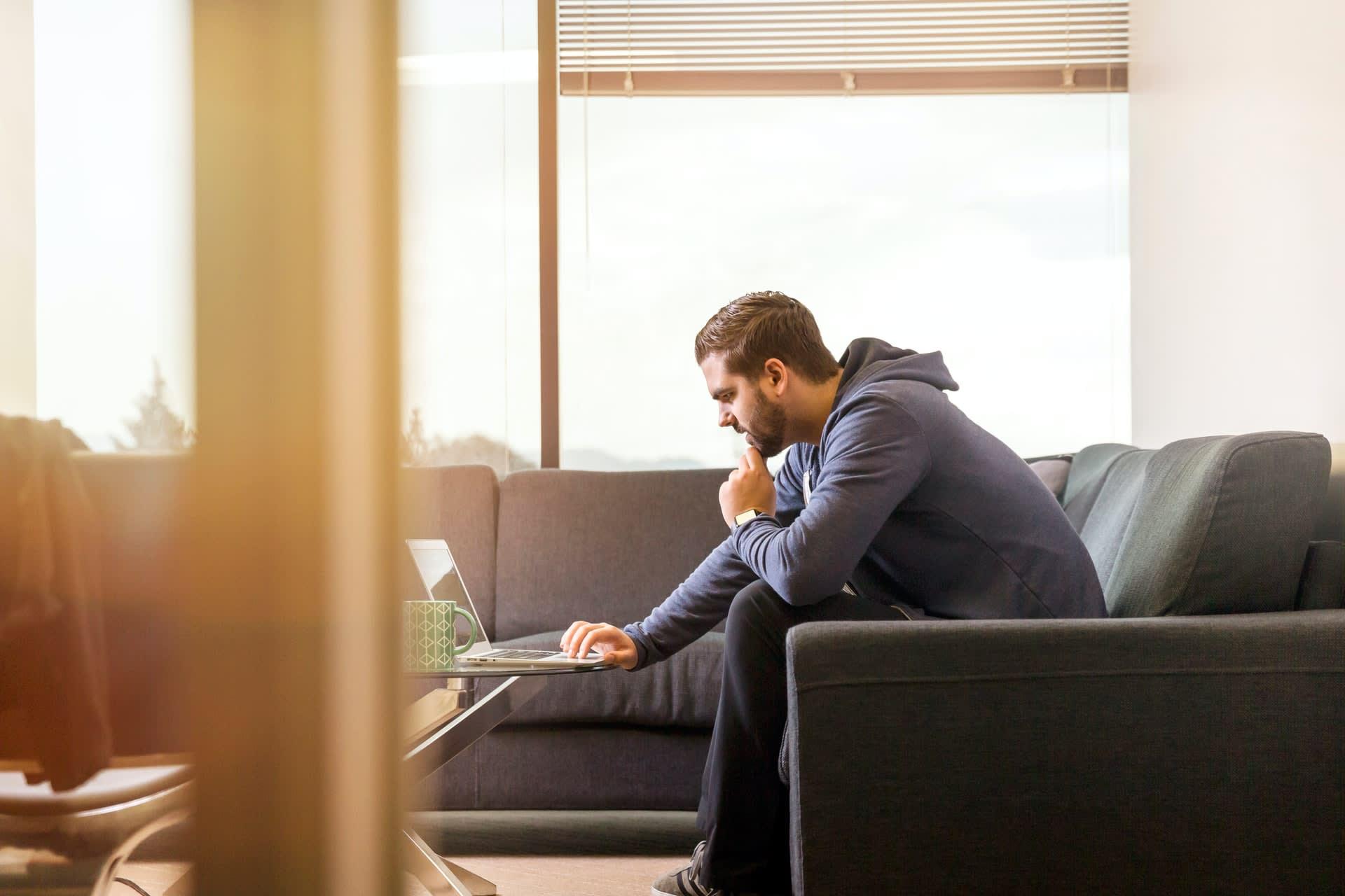 Man on laptop sitting on sofa