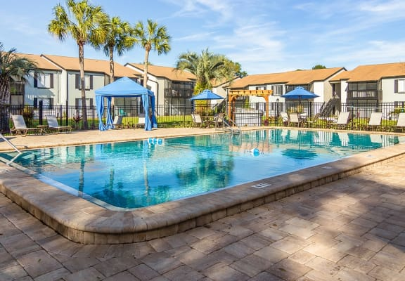 Pool pavilion with sundeck, shaded cabanas and lounge chairs at The Oaks on Monument apartments in Jacksonville, FL