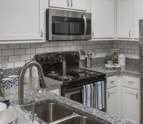 Kitchen with stainless steel appliances and granite countertops and tile backsplash