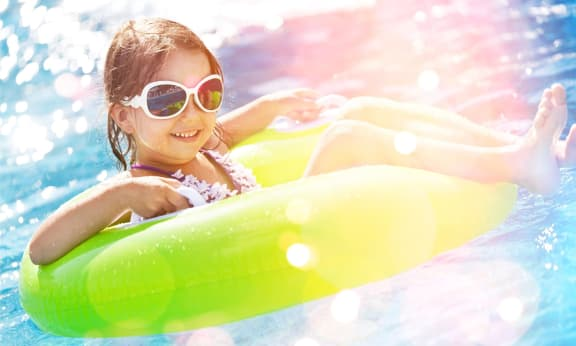 Little Girl in Sunglasses Laying in Inner Tube in Pool and Smiling