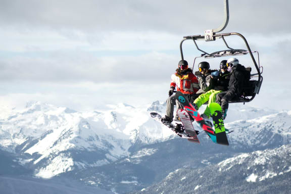 Group of People Taking Ski Lift on Snowy Mountain