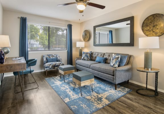 Comfortable living room with grey couch and ottomans in an apartment for rent at Forest Ridge apartments for rent in Macon, GA
