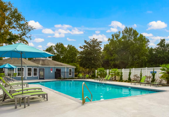 Swimming pool with cement sundeck that has lounge chairs and umbrellas at Azure Cove Apartments