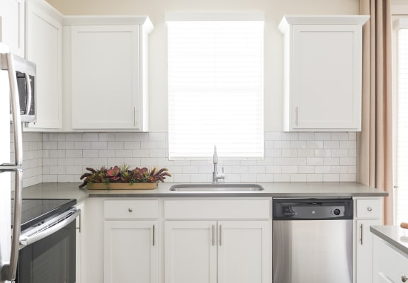 Kitchen With White Cabinetry And Appliances at RivuletApartments, American Fork, Utah