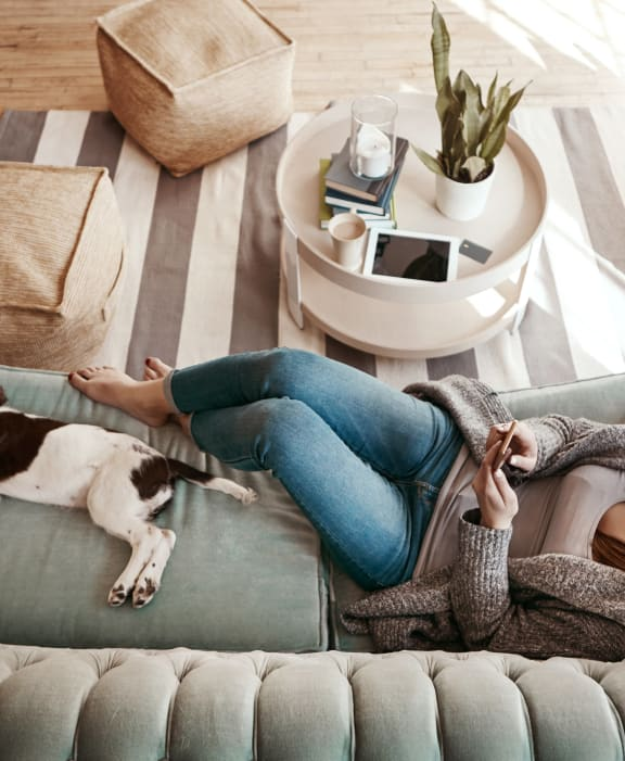 Woman Lounging on Couch with Dog at Oak Pointe Apartments in Fremont, CA