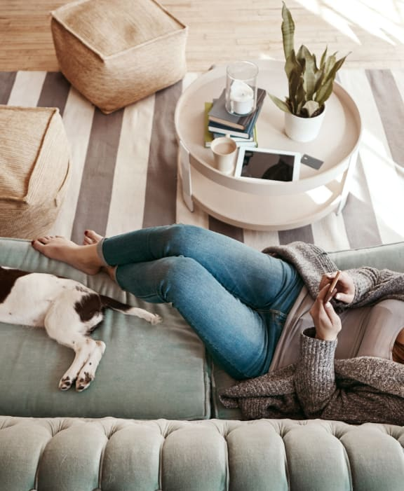 Woman Lounging on Couch with Dog at 1038 on Second Apartments in Lafayette, CA