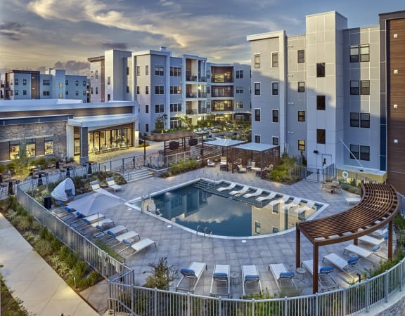 Overview of commuhnty with pool, outdoor lounge and apartment buildings