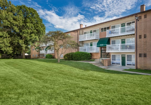 Park Green Apartments overlooking a spacious community yard with lush greenery, trees, and private balconies.