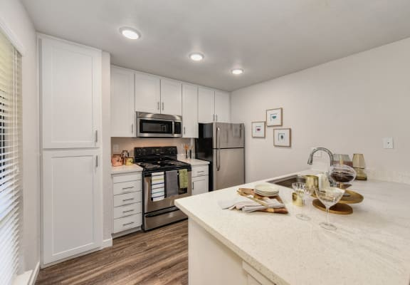 Kitchen with White Cabinents, Hardwood Inspired Floor, Dishwasher and Refrigerator