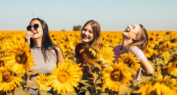three women in sunflower field