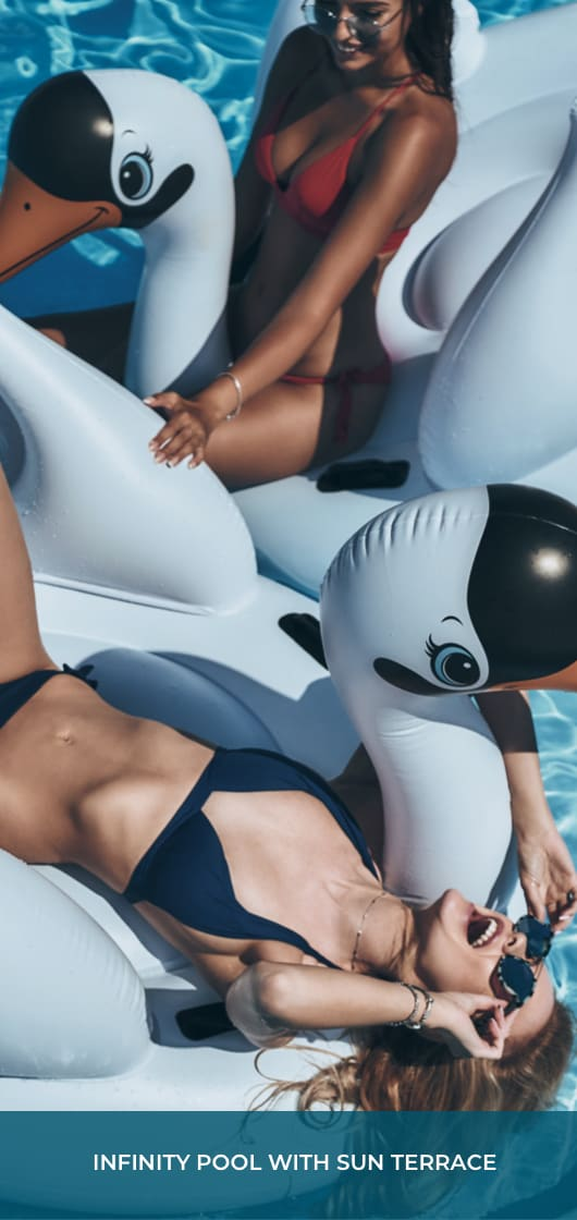 """two young women on swan floatation devices in a pool and text that says """"Infinity Pool with Sun Terrace"""""""
