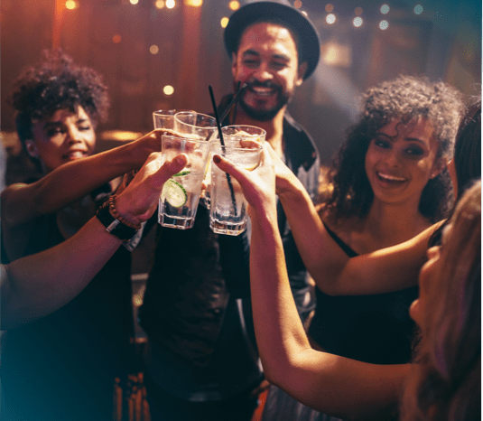 a group of young people toasting with drinks