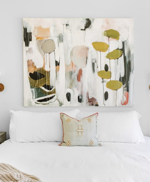 White bed next to picture art showing greenery