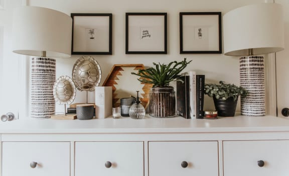 Dresser with lamps, trinkets, plants,a nd pictures hanging