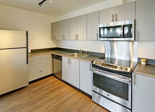 Updated L-shaped kitchen with fridge, dishwasher, sink, oven and microwave from left to right. All appliances are stainless steel and area has wood style flooring.