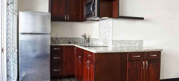 Waikiki Walina Apartments kitchen area with appliances, cabinets, and counters