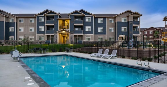 Pool with lounge chairs and apt buildings Spokane WA 99224 l Copper River Apts For Rent
