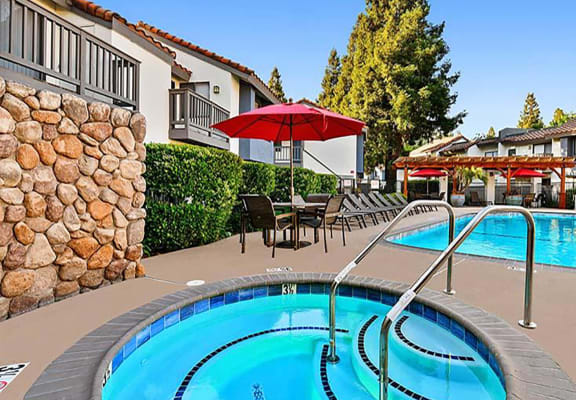 Hot tub and pool with apartments in background