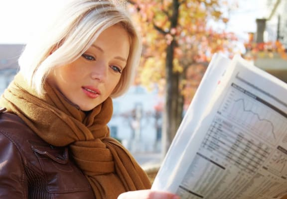 Woman reading the paper Antioch CA Apts For Rent at Twin Creeks