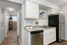 Renovated Kitchen with White Tile Backsplash and Stainless Steel Dishwasher and Fridge
